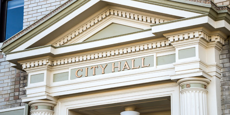 A close up of a City Hall sign
