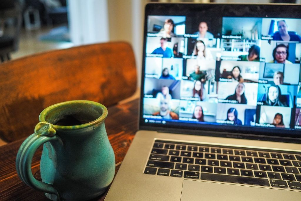 Zoom meeting on computer screen with coffee mug to left